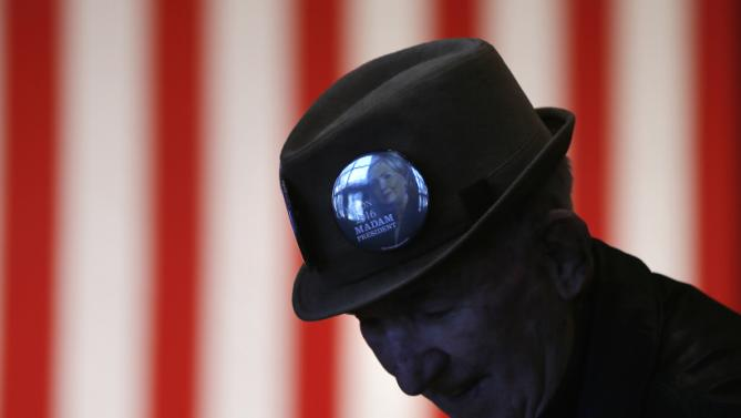 Wearing a Hillary Clinton button on his hat, James Johnston takes his seat before her husband, former President Bill Clinton spoke at a campaign stop for the Democratic presidential candidate, Wednesday, Jan. 13, 2016, at Keene State College in Keene, N.H. (AP Photo/Matt Rourke)
