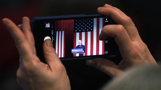 An attendee snaps a photo of former President Bill Clinton as he speaks during a campaign stop for his wife, Democratic presidential candidate Hilary Clinton, Wednesday, Jan. 13, 2016, at Keene State College in Keene, N.H. (AP Photo/Matt Rourke)