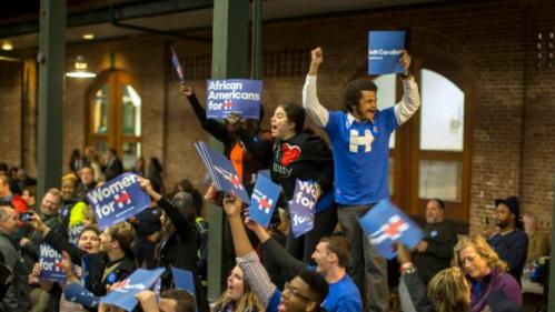 Supporters wave signs and shout while they wait for Democratic presidential candidate Hillary Rodham Clinton to arrive at the Jim Clyburn Fish Fry, on Saturday, Jan. 16, 2016, at the Charleston Visitor Center in Charleston, S.C. (AP Photo/Stephen B. Morton)