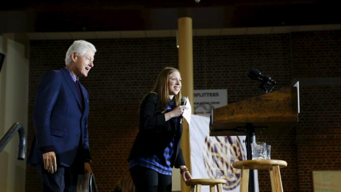 Former U.S. President Bill Clinton, accompanied by his daughter Chelsea, takes the stage at Abraham Lincoln High School while campaigning for his wife, U.S. Democratic presidential candidate Hillary Clinton, in Des Moines, Iowa, January 16, 2016. REUTERS/Aaron P. Bernstein