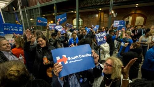 Supporters wave signs, as they dance and sing while they wait for Democratic presidential candidate Hillary Rodham Clinton to arrive at the Jim Clyburn Fish Fry, on Saturday, Jan. 16, 2016, at the Charleston Visitor Center in Charleston, S.C. (AP Photo/Stephen B. Morton)