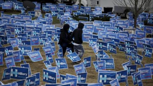 People walk through a maze of political signs for Hillary Clinton and Democratic opponent Bernie Sanders outside the Gaillard Center before the start of the NBC News-YouTube Democratic Debate in Charleston, South Carolina, January 17, 2016. REUTERS/Randall Hill