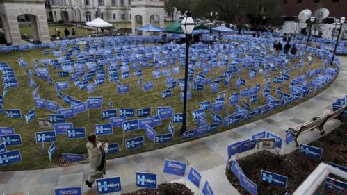 People walk past a maze of political signs for Hillary Clinton and Democratic opponent Bernie Sanders outside the Gaillard Center before the start of the NBC News-YouTube Democratic Debate in Charleston, South Carolina, January 17, 2016. REUTERS/Randall Hill