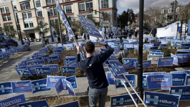A Hillary Clinton supporter walks through a maze of political signs for Clinton and Democratic opponent Bernie Sanders outside the Gaillard Center before the start of the NBC News-YouTube Democratic Debate in Charleston, South Carolina, January 17, 2016. REUTERS/Randall Hill