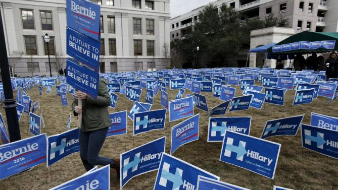 A Bernie Sanders supporter carries a sign through a maze of political sign for Sanders and opponent Hillary Clinton before the start of the NBC News-YouTube Democratic Debate in Charleston, South Carolina, January 17, 2016. REUTERS/Randall Hill