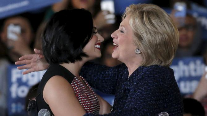 U.S. Democratic presidential candidate Hillary Clinton is greeted by singer Demi Lovato as she arrives at a campaign event in Iowa City, Iowa, United States, January 21, 2016.   REUTERS/Jim Young