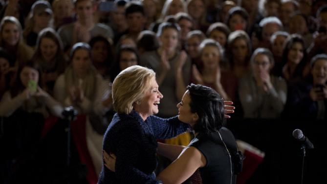 Democratic presidential candidate Hillary Clinton, left, hugs musician Demi Lovato after her speech during a rally on the campus of University of Iowa Thursday, Jan. 21, 2016, in Iowa City, Iowa. (AP Photo/Jae C. Hong)