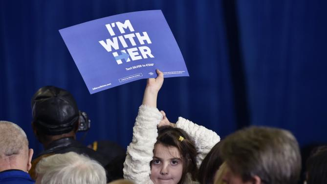 A girl waves a placard as former President Bill Clinton speaks at a campaign event for his wife, Democratic presidential candidate Hillary Clinton, on Thursday, Jan. 21, 2016, in Las Vegas. (AP Photo/David Becker)