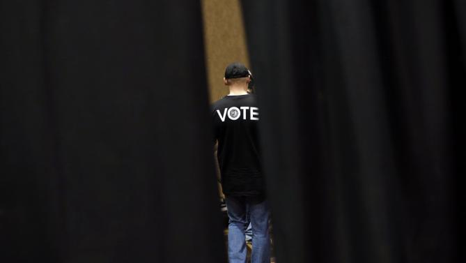A supporter of Democratic presidential candidate Hillary Clinton is seen through a curtain as he walks backstage before a campaign event featuring Clinton in Burlington, Iowa, Wednesday, Jan. 20, 2016. (AP Photo/Patrick Semansky)