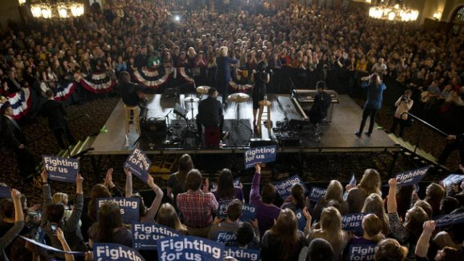 Democratic presidential candidate Hillary Clinton, center, joined by musician Demi Lovato, speaks during a rally on the campus of University of Iowa Thursday, Jan. 21, 2016, in Iowa City, Iowa. (AP Photo/Jae C. Hong)