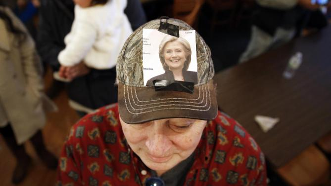 Retired teacher Rich Fullerton has an image of Democratic presidential candidate Hillary Clinton taped to his cap as he listens to Clinton during a campaign event at Danceland Ballroom in Davenport, Iowa, Saturday, Jan. 23, 2016. (AP Photo/Patrick Semansky)