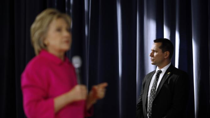Sunlight shines on a member of the U.S. Secret Service, right, as Democratic presidential candidate Hillary Clinton speaks during a town hall at Eagle Heights Elementary School in Clinton, Iowa, Saturday, Jan. 23, 2016. (AP Photo/Patrick Semansky)