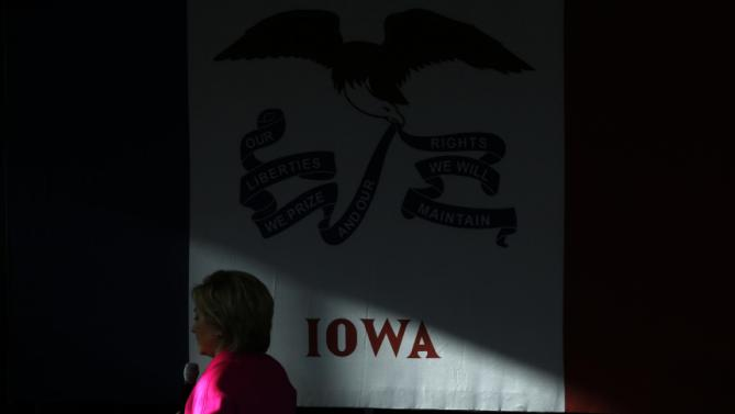 A patch of sunlight shines on the Iowa state flag as Democratic presidential candidate Hillary Clinton speaks during a town hall at Eagle Heights Elementary School in Clinton, Iowa, Saturday, Jan. 23, 2016. (AP Photo/Patrick Semansky)