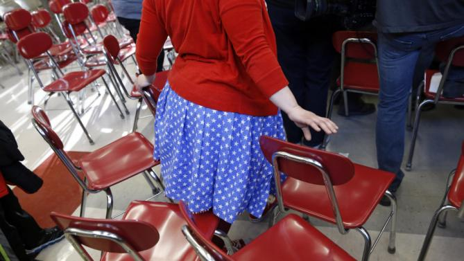 A woman wearing patriotic colors makes her way through chairs to get a closer view of Democratic presidential candidate Hillary Clinton after a town hall at Eagle Heights Elementary School in Clinton, Iowa, Saturday, Jan. 23, 2016. (AP Photo/Patrick Semansky)