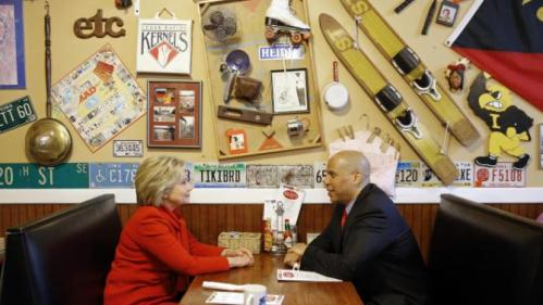 Democratic presidential candidate Hillary Clinton, left, chats with Sen. Cory Booker, D-N.J., at Riley's Cafe in Cedar Rapids, Iowa, Sunday, Jan. 24, 2016. (AP Photo/Patrick Semansky)