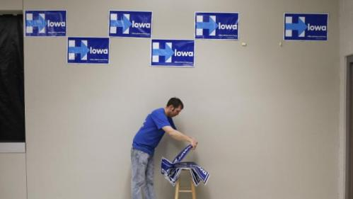 Shawn Stender removes campaign signs for Democratic presidential candidate Hillary Clinton after a town hall featuring Clinton at Vernon Middle School in Marion, Iowa, Sunday, Jan. 24, 2016. (AP Photo/Patrick Semansky)