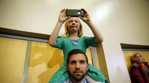 Charlotte Huebsch, 7, of Ankeny, Iowa, takes a photo while sitting on the shoulders of her dad, Ben Huebsch, as Democratic U.S. presidential candidate Hillary Clinton speaks during a Get Out the Caucus event at the Valley Southwoods Freshman High School in West Des Moines, Iowa, January 24, 2016. REUTERS/Scott Morgan