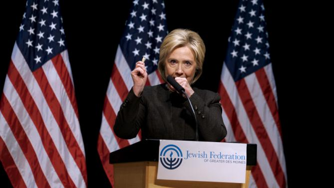 Democratic presidential candidate Hillary Clinton holds up a lozenge as she struggles to contain a coughing fit as she speaks at the Jewish Federation of Greater Des Moines while campaigning in Des Moines, Iowa January 25, 2016.   REUTERS/Rick Wilking
