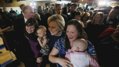 U.S. Democratic presidential candidate Hillary Clinton poses with two supporters and their babies during a campaign stop at the Adel Family Fun Center bowling alley in Adel, Iowa January 27, 2016. REUTERS/Jim Bourg