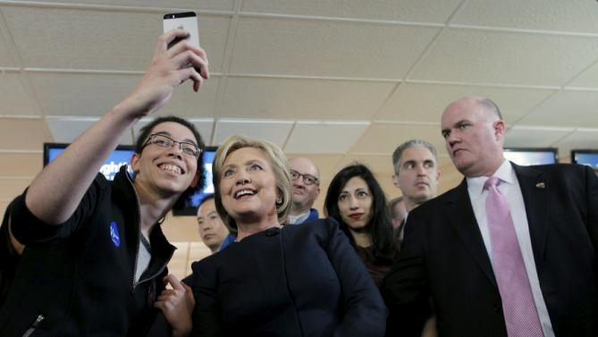 U.S. Democratic presidential candidate Hillary Clinton poses for a selfie with an audience member at a campaign stop at the Family Fun Center in Adel, Iowa January 27, 2016.  REUTERS/Brian Snyder