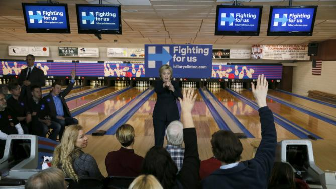 U.S. Democratic presidential candidate Hillary Clinton points at people in the crowd raising their hands that they are still paying off high interest rate student loan debt during a campaign stop at the Adel Family Fun Center bowling alley in Adel, Iowa January 27, 2016. REUTERS/Jim Bourg