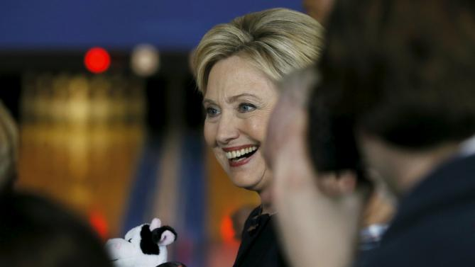U.S. Democratic presidential candidate Hillary Clinton holds a stuffed cow toy given to her by a supporter in the crowd during a campaign stop at the Adel Family Fun Center bowling alley in Adel, Iowa January 27, 2016. REUTERS/Jim Bourg