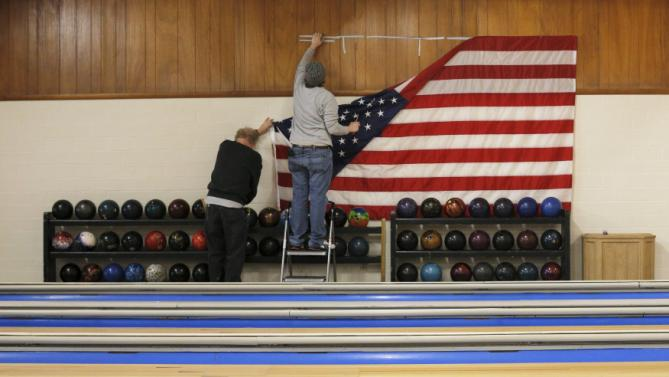 Workers take down a U.S. flag following a campaign stop by U.S. Democratic presidential candidate Hillary Clinton at the Family Fun Center in Adel, Iowa January 27, 2016.  REUTERS/Brian Snyder