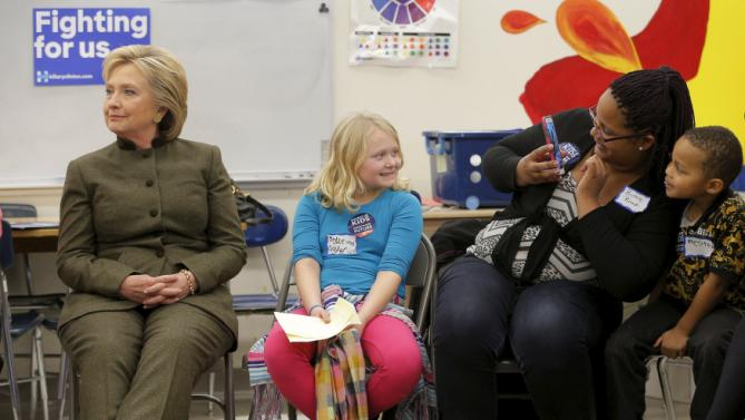 A girl poses for a photograph next to U.S. Democratic presidential candidate Hillary Clinton during a meeting with the group Every Child Matters at the Berg Middle School in Newton, Iowa January 28, 2016. REUTERS/Brian Snyder