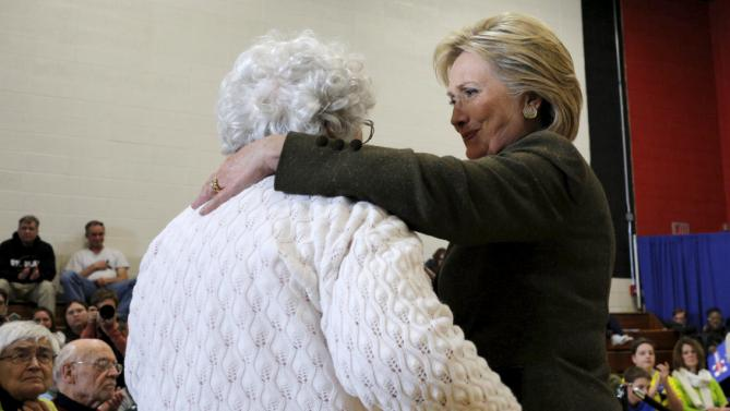 U.S. Democratic presidential candidate Hillary Clinton embraces 73 year-old Annette Bebout, after listening to Bebout relate how she lost her home, during a campaign stop at Berg Middle School in Newton, Iowa January 28, 2016. REUTERS/Brian Snyder