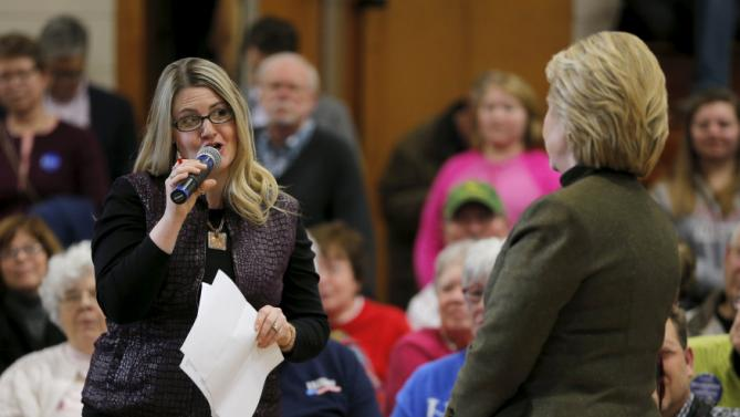 An audience member talks about student debt with U.S. Democratic presidential candidate Hillary Clinton during a campaign stop at the Berg Middle School in Newton, Iowa January 28, 2016. REUTERS/Brian Snyder