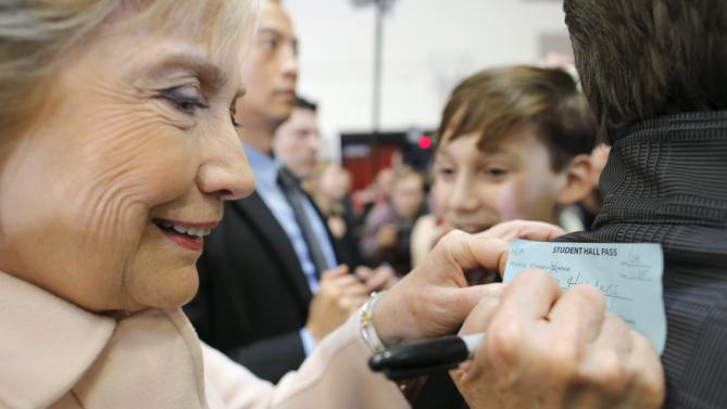 U.S. Democratic presidential candidate Hillary Clinton signs 13-year-old Noah Harkness' hall pass after Harkness got out of classes to attend a rally at Grand View University in Des Moines, Iowa January 29, 2016. REUTERS/Brian Snyder TPX IMAGES OF THE DAY