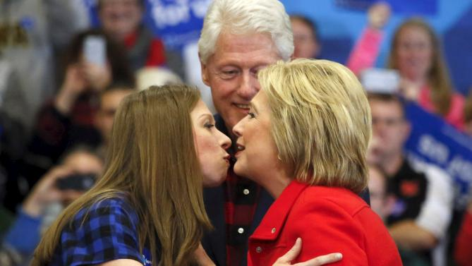 U.S. Democratic presidential candidate Hillary Clinton (R) kisses her daughter Chelsea Clinton (L) as former U.S. President Bill Clinton is seen in the background during a campaign rally at Washington High School in Cedar Rapids, Iowa January 30, 2016.  REUTERS/Adrees Latif         TPX IMAGES OF THE DAY