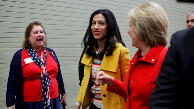 """U.S. Democratic presidential candidate Hillary Clinton and her aide Huma Abedin walk away after an off-schedule stop at the """"I'll Make Me a World in Iowa Celebration Day"""" in Des Moines, Iowa January 30, 2016. REUTERS/Brian Snyder"""
