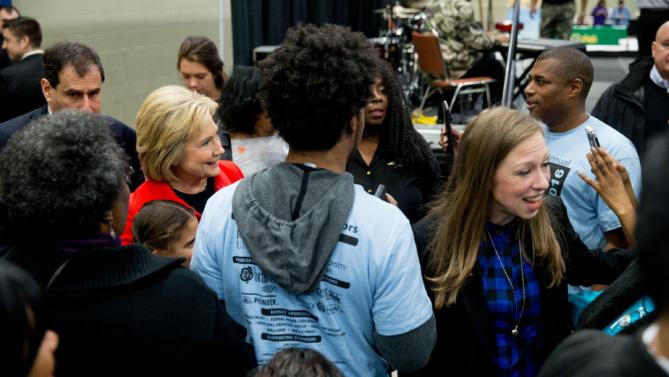 Democratic presidential candidate Hillary Clinton, center, and her daughter Chelsea Clinton, right, greet visitors to the African American Festival, I'll Make Me a World Celebration Day at the Iowa Events Center in Des Moines, Iowa, Saturday, Jan. 30, 2016. (AP Photo/Andrew Harnik)