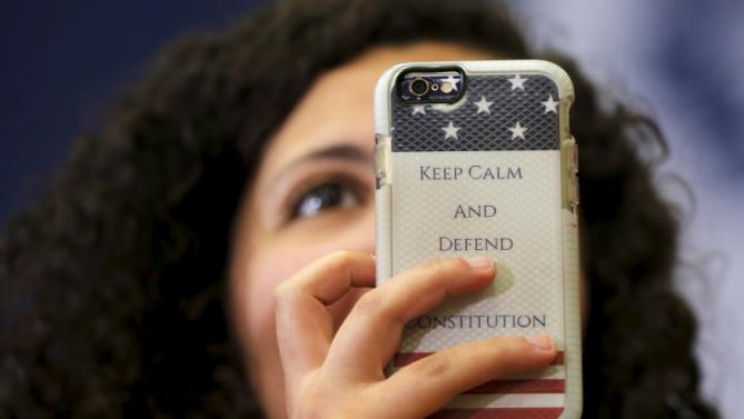 "An audience member holds up a phone with a case reading ""Keep Calm and Defend the Constitution"" during a ""Get Out to Caucus"" rally with U.S. Democratic presidential candidate Hillary Clinton in Cedar Rapids, Iowa January 30, 2016.  REUTERS/Brian Snyder"
