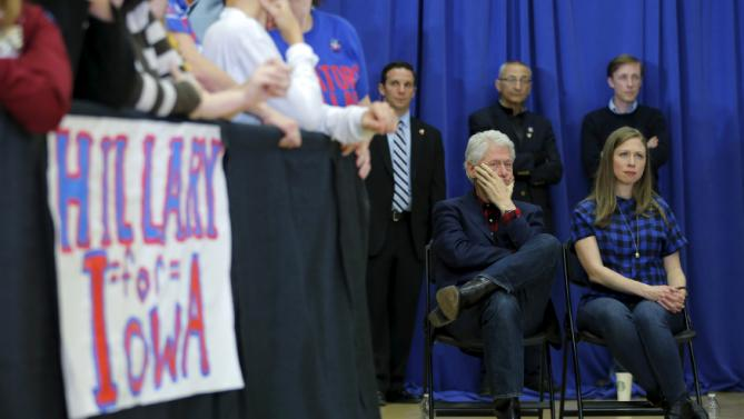 "Former U.S. President Bill Clinton and his daughter Chelsea listen as U.S. Democratic presidential candidate Hillary Clinton speaks during a ""Get Out to Caucus"" rally in Cedar Rapids, Iowa January 30, 2016.  REUTERS/Brian Snyder"