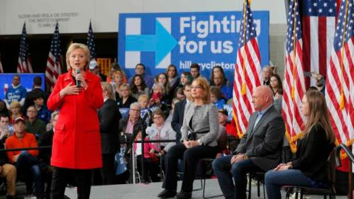 """U.S. Democratic presidential candidate Hillary Clinton speaks as her daughter Chelsea Clinton sits with Gabby Giffords and her husband Mark Kelly during a """"Get Out to Caucus"""" rally at Iowa State University in Ames, Iowa January 30, 2016. The New York Times's editorial board endorsed Democrat Hillary Clinton and Republican John Kasich as they seek to become their parties' nominees in the U.S. presidential election, calling Clinton one of the most """"deeply qualified presidential candidates in modern history."""" REUTERS/Brian Snyder"""