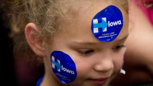A young member of the audience wears campaign stickers before Democratic presidential candidate Hillary Clinton, accompanied by former President Bill Clinton and their daughter Chelsea Clinton, arrive to speak at a rally at Washington High School in Cedar Rapids, Iowa, Saturday, Jan. 30, 2016. (AP Photo/Andrew Harnik)