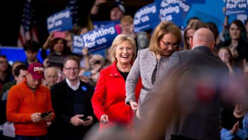 Democratic presidential candidate Hillary Clinton, center, accompanied by former Arizona Rep. Gabby Giffords, second from right, and her husband Mark Kelly, right, arrives for a rally at Iowa State University in Ames, Iowa Saturday, Jan. 30, 2016(AP Photo/Andrew Harnik)