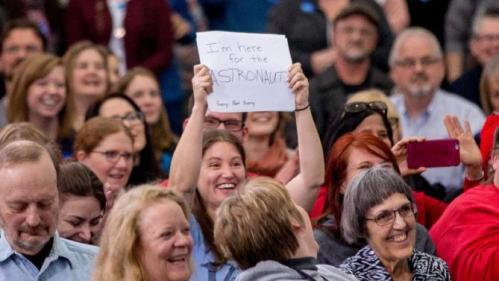 """A woman in the audience holds a sign that reads """"I'm here for the astronaut"""" as former Arizona Rep. Gabby Giffords and her husband Mark Kelly, joins Democratic presidential candidate Hillary Clinton for a rally at Iowa State University in Ames, Iowa Saturday, Jan. 30, 2016(AP Photo/Andrew Harnik)"""