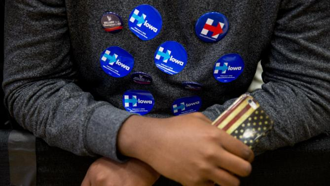 A supporter wears campaign stickers on his chest before Democratic presidential candidate Hillary Clinton, accompanied by former President Bill Clinton and their daughter Chelsea Clinton, arrives to speak at a rally at Washington High School in Cedar Rapids, Iowa, Saturday, Jan. 30, 2016. (AP Photo/Andrew Harnik)
