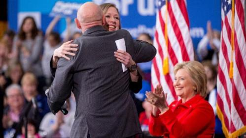 Democratic presidential candidate Hillary Clinton, right, applauds as her daughter Chelsea Clinton, who gets a hug from Mark Kelly, left, during a rally at Iowa State University in Ames, Iowa Saturday, Jan. 30, 2016. (AP Photo/Andrew Harnik)