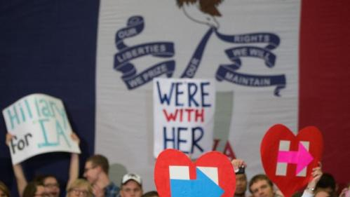 Members of the audience hold signs in front of a large Iowa state flag as Democratic presidential candidate Hillary Clinton speaks at a rally at Washington High School in Cedar Rapids, Iowa, Saturday, Jan. 30, 2016. (AP Photo/Andrew Harnik)