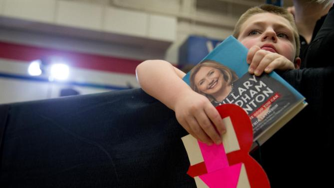 A young member of the audience holds a campaign sign and a copy of a book about Democratic presidential candidate Hillary Clinton as she speaks at a rally at Washington High School in Cedar Rapids, Iowa, Saturday, Jan. 30, 2016. (AP Photo/Andrew Harnik)