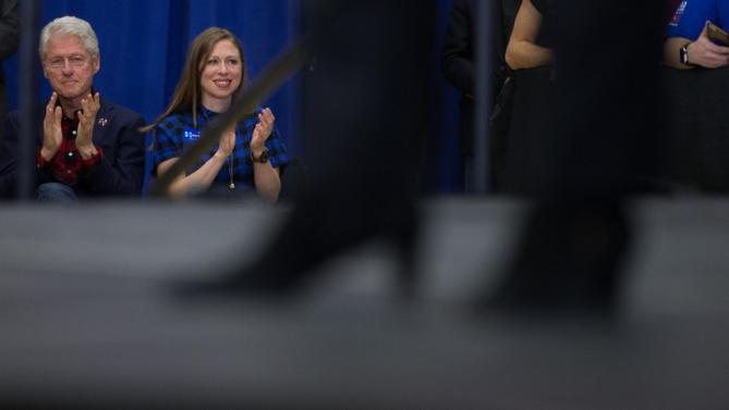 Former President Bill Clinton and daughter Chelsea Clinton applauds as Democratic presidential candidate Hillary Clinton, foreground, speaks at a rally at Washington High School in Cedar Rapids, Iowa, Saturday, Jan. 30, 2016. (AP Photo/Andrew Harnik)