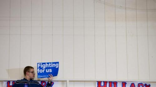 A member of the audience holds a campaign sign at the top of a set of bleachers as Democratic presidential candidate Hillary Clinton speaks at a rally at Washington High School in Cedar Rapids, Iowa, Saturday, Jan. 30, 2016. (AP Photo/Andrew Harnik)