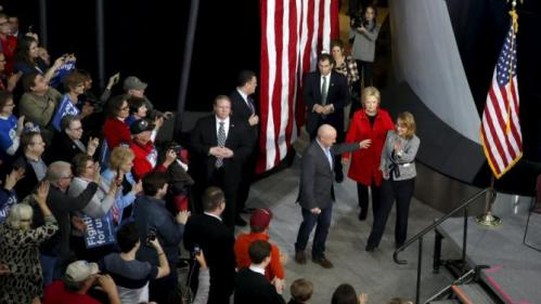 U.S. Democratic presidential candidate Hillary Clinton (C), in red, arrives to a campaign rally with Gabby Giffords (R) and her husband Mark Kelly (L) at Iowa State University in Ames, Iowa January 30, 2016. REUTERS/Adrees Latif