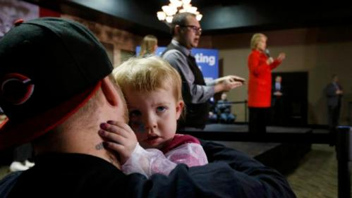 A young child hugs her father as U.S. Democratic presidential candidate Hillary Clinton (R) addresses a campaign event in Carroll, Iowa January 30, 2016. REUTERS/Jim Bourg
