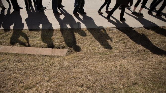 Visitors wait in line outside a rally for Democratic presidential candidate Hillary Clinton at Abraham Lincoln High School in Council Bluffs, Iowa, Sunday, Jan. 31, 2016. (AP Photo/Andrew Harnik)