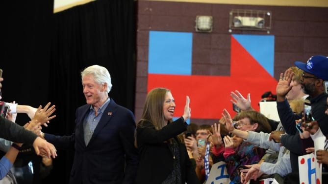 Former President Bill Clinton, accompanied by his daughter Chelsea Clinton, arrive for a Democratic presidential candidate Hillary Clinton rally at Abraham Lincoln High School in Des Moines, Iowa, Sunday, Jan. 31, 2016. (AP Photo/Andrew Harnik)